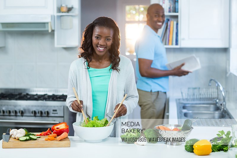 Woman preparing food while man standing in the background at kitchen