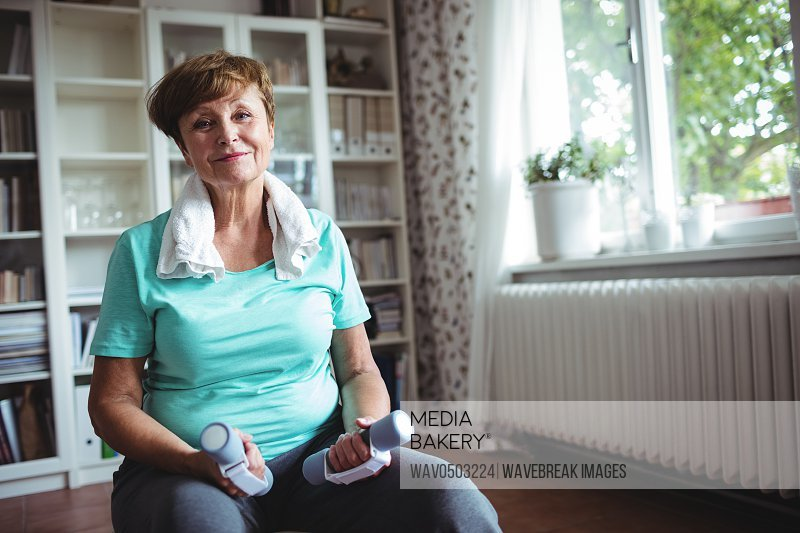 Portrait of senior woman sitting on exercise ball with dumbbells at home