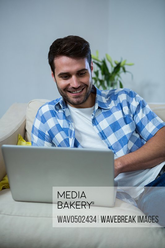 Man using laptop while relaxing on sofa at home