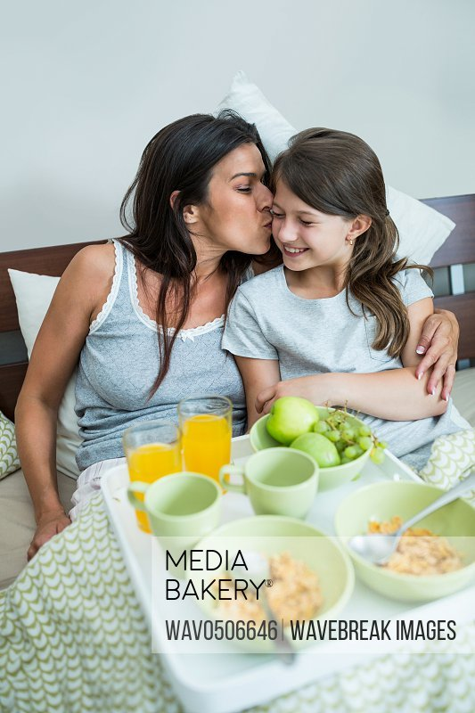 Mother kissing on daughter cheeks while having breakfast on bed at home