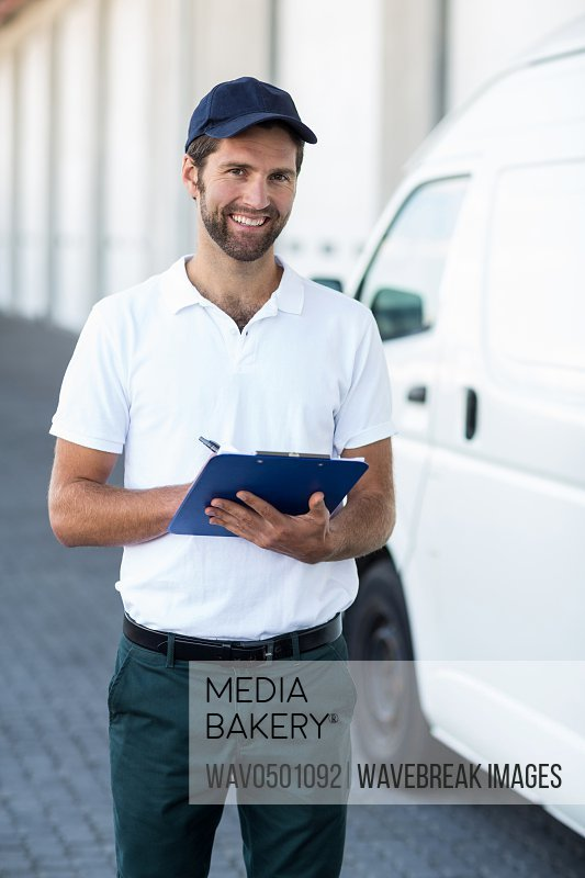 Portrait of delivery man holding a clipboard next to his van outside the warehouse
