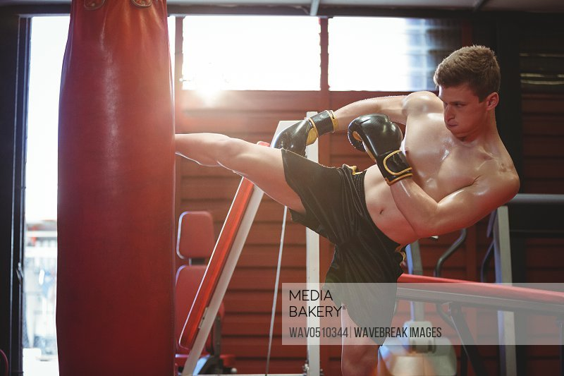 Boxer practicing kickboxing in fitness studio