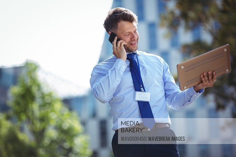 Handsome businessman holding laptop and talking on mobile phone