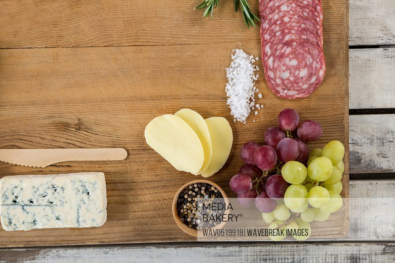 Roquefort cheese grapes and ham with various ingredients on chopping board