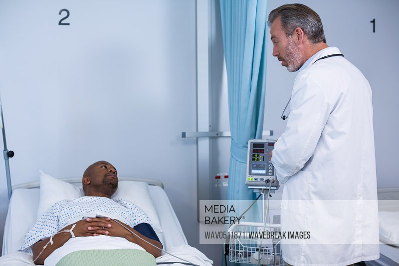 Doctor interacting with patient during visit in ward of hospital