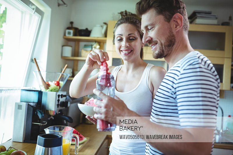 Smiling couple preparing watermelon smoothie in kitchen at home