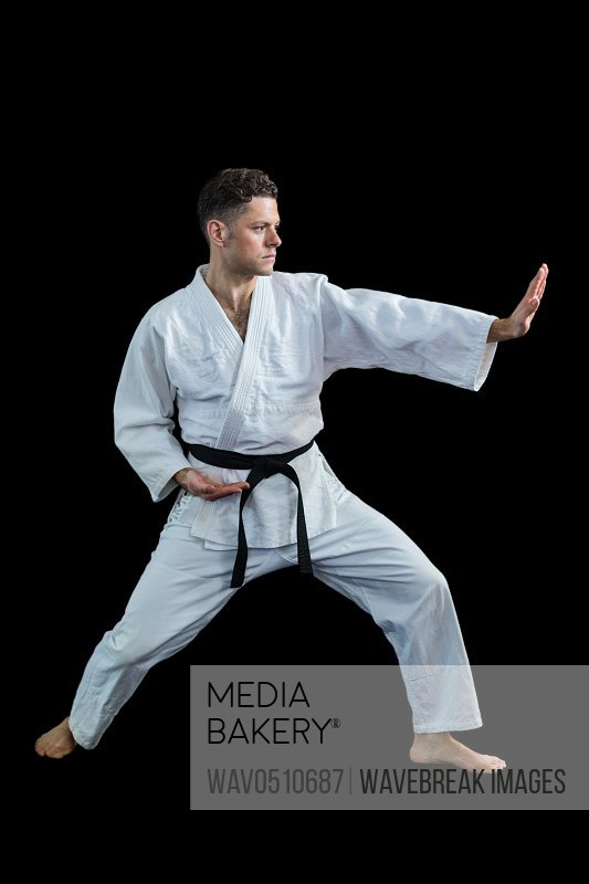 Karate player performing karate stance against black background
