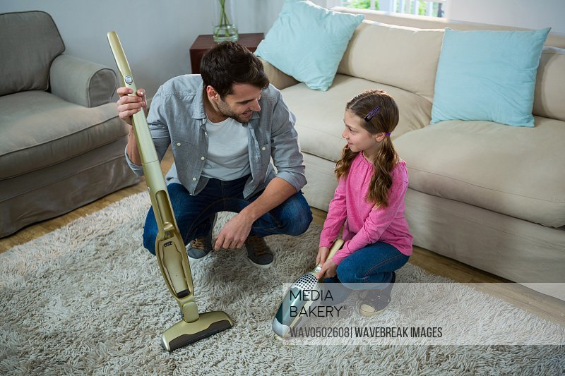 Daughter helping father to clean carpet with a vacuum cleaner at home