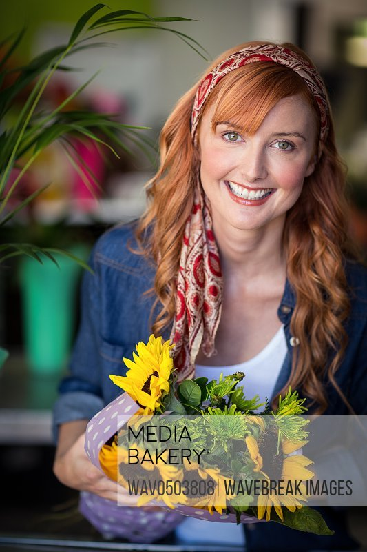 Portrait of smiling female florist holding bunch of flower in flower shop