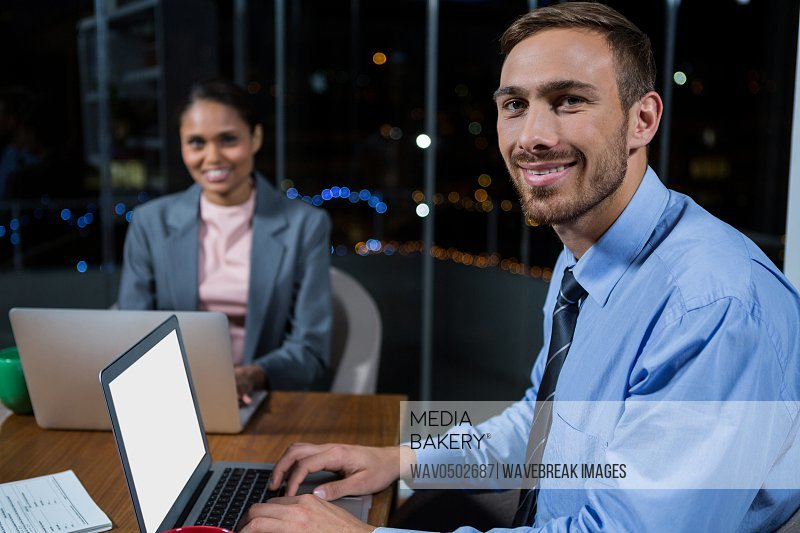 Portrait of businessman and businesswoman working in office at night