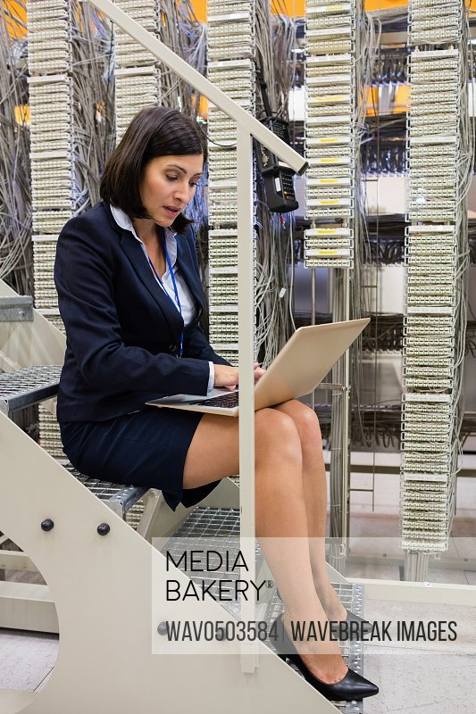 Attentive technician sitting on steps using laptop in server room