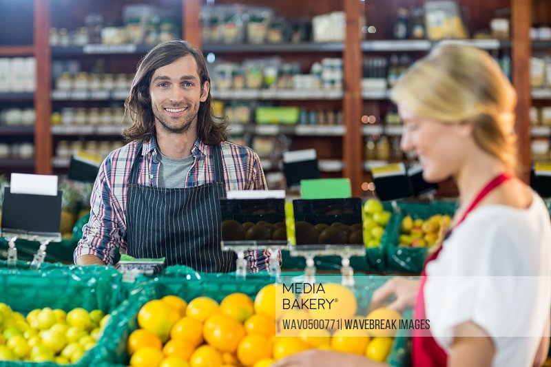Portrait of smiling staffs checking fruits in organic section of supermarket
