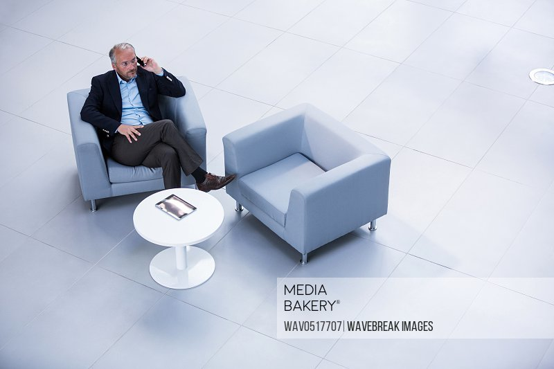 Businessman sitting on a chair and talking on mobile phone