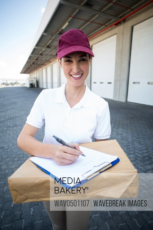 Portrait of delivery woman holding a clipboard and parcel outside the warehouse
