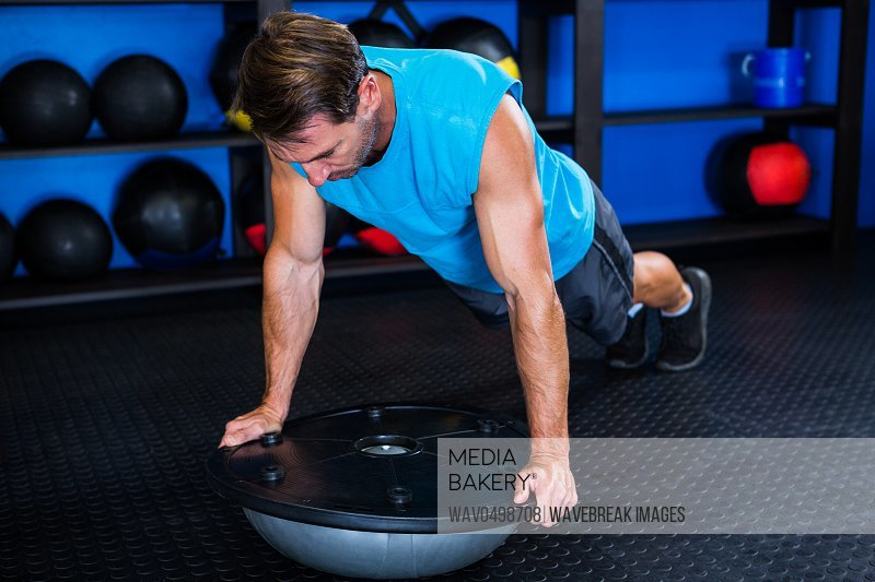 Young man with BOSU ball while exercising in gym