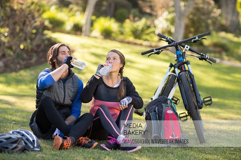 Biker couple relaxing and having water in countryside park