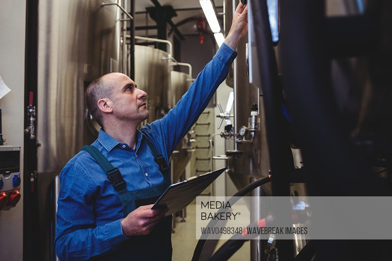 Side view of male manufacturer examining machinery at brewery