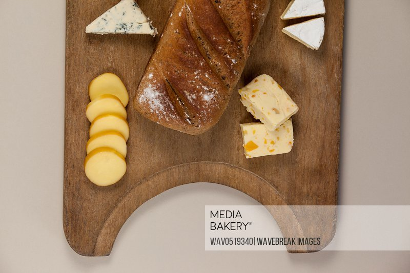 Variety of cheese with bread on chopping board