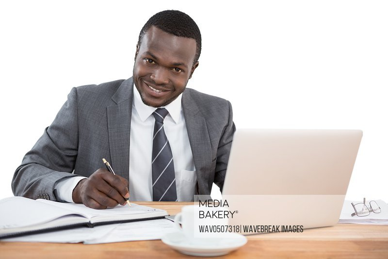 Happy businessman working at office desk against white background