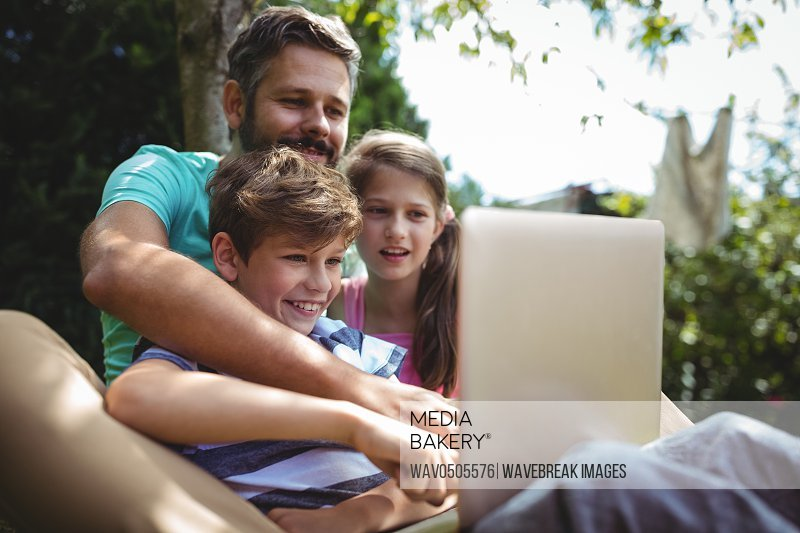 Happy father and kids using laptop in garden