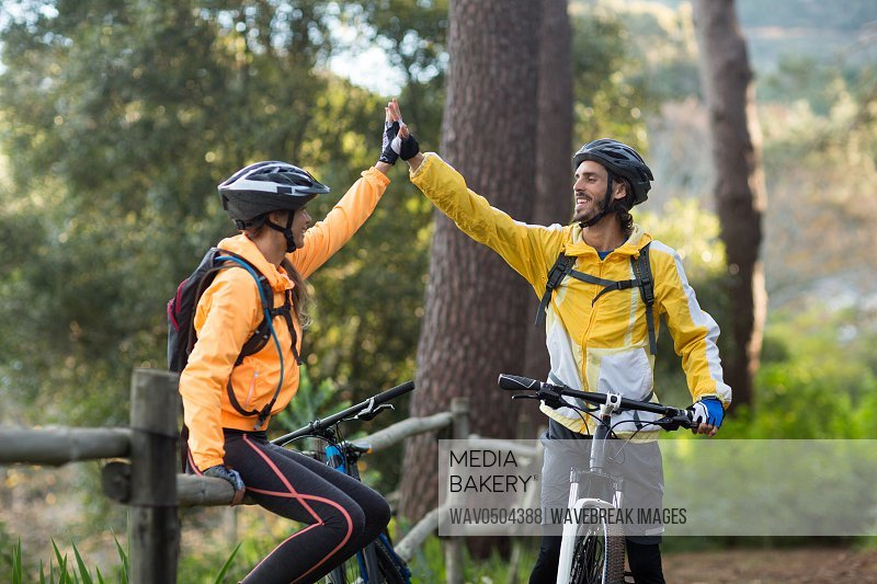 Happy biker couple giving high five to each other in countryside