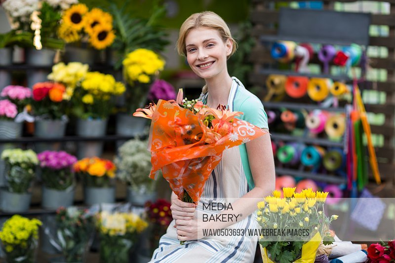 Portrait of happy female florist holding flower bouquet in the shop