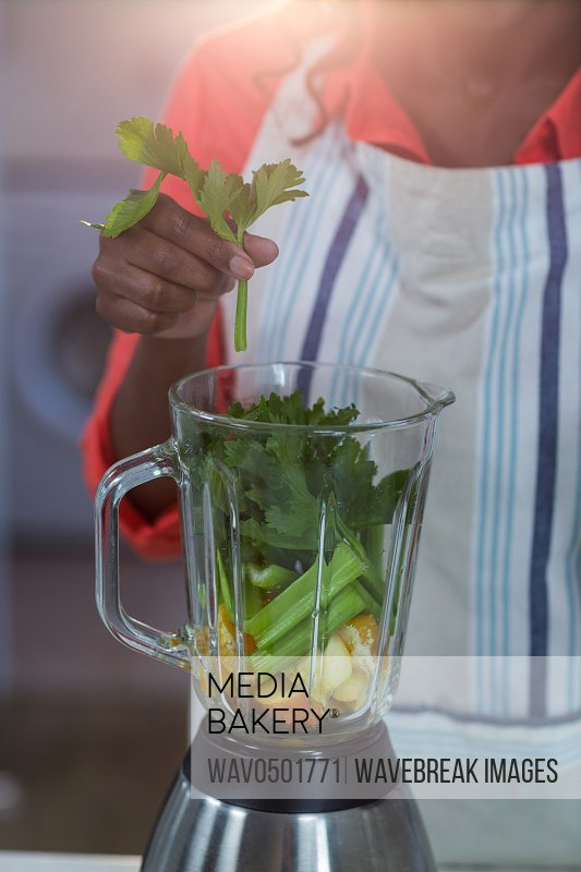 Mid-section of woman putting vegetable in a mixer in kitchen