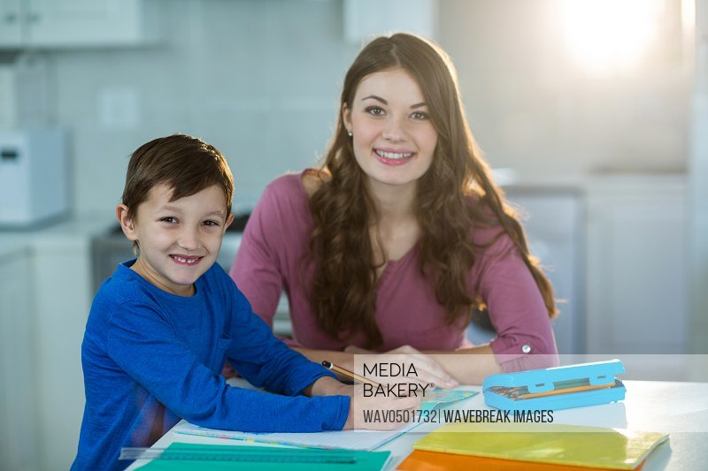 Mother helping her son with homework at home