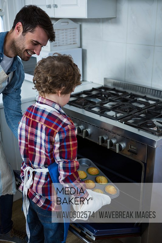 Father and son placing cupcakes tray in oven in the kitchen