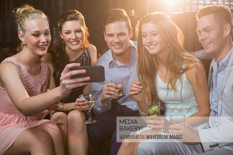 Smiling friends taking a selfie from mobile phone while having cocktail in bar