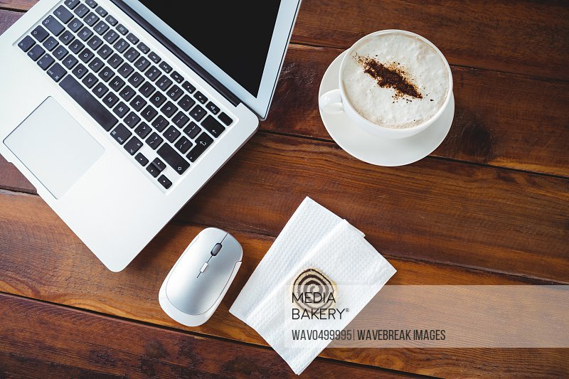 Close-up of coffee cup and laptop on a table in cafeteria