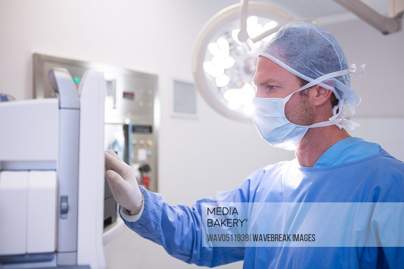 Male surgeon using machine in operation theater at hospital