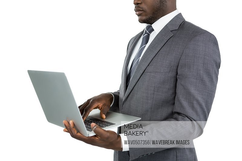 Mid section of businessman using laptop against white background