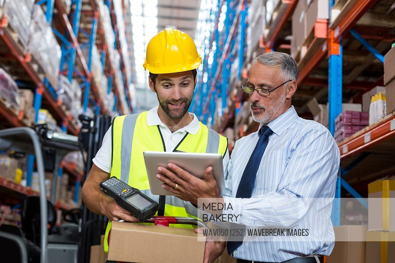 Warehouse manager with interacting male worker over digital tablet in warehouse