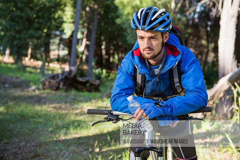 Male mountain biker standing with bicycle in the forest