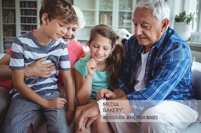 Grandparents and grandchildren looking at smartwatch in living room at home