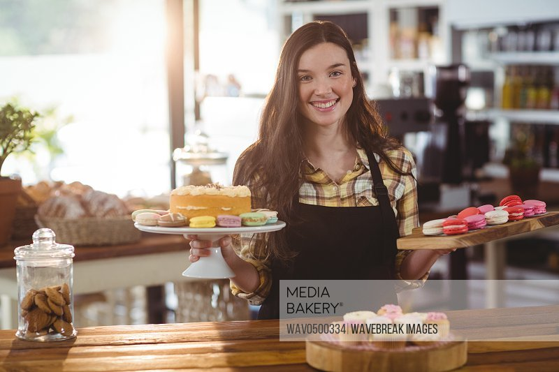 Portrait of waitress standing at counter with desserts in cafe