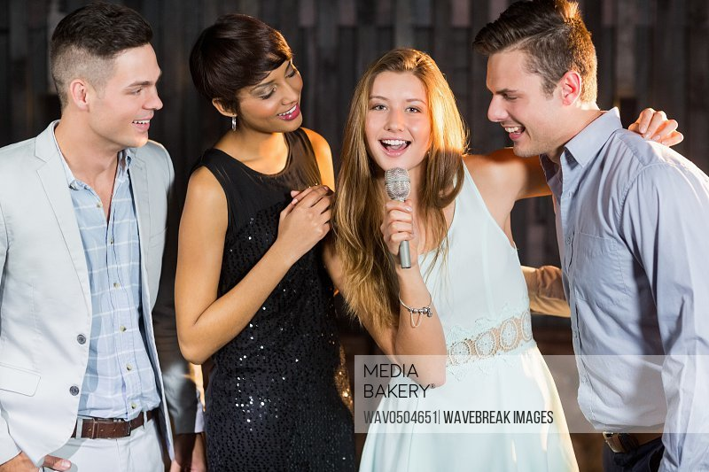 Happy friends singing song together in bar