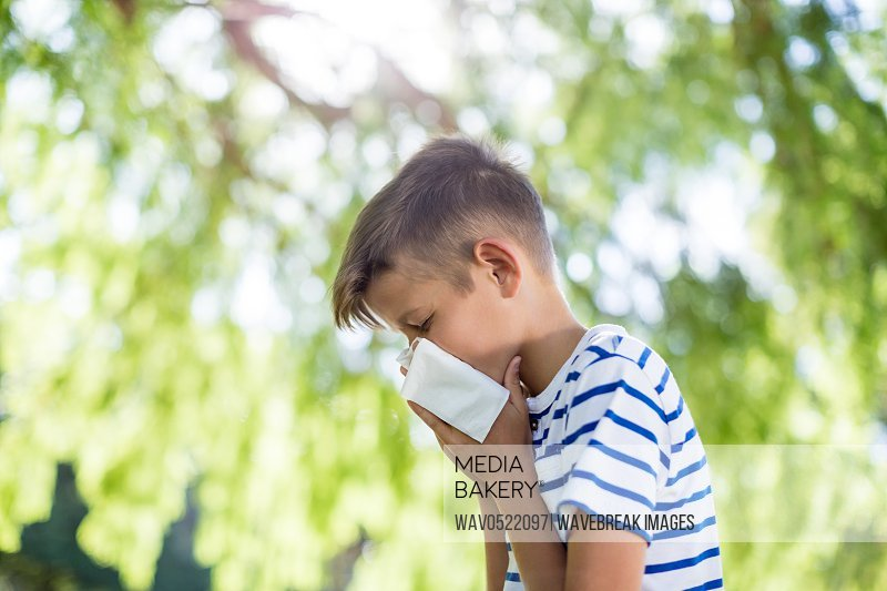Boy wiping his nose while sneezing