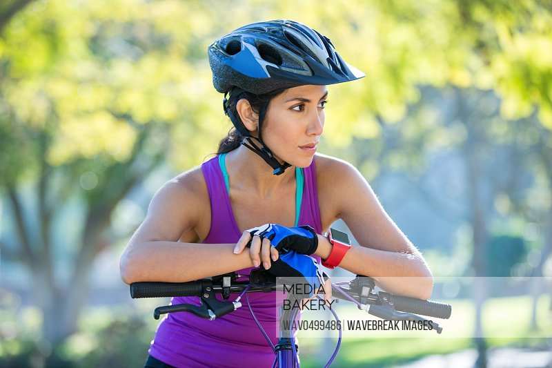Thoughtful female athletic leaning on bicycle in countryside