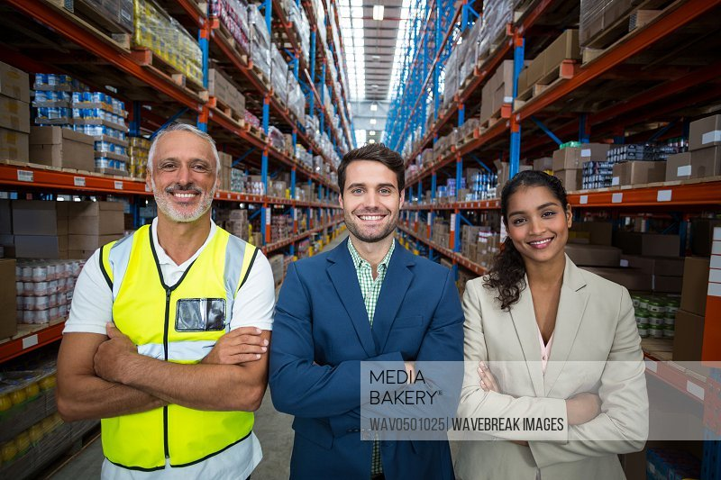 Portrait of warehouse team standing with arms crossed in warehouse