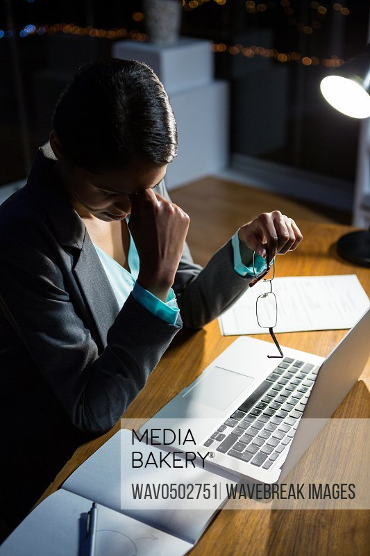 Stressed businesswoman sitting at her desk in the office at night