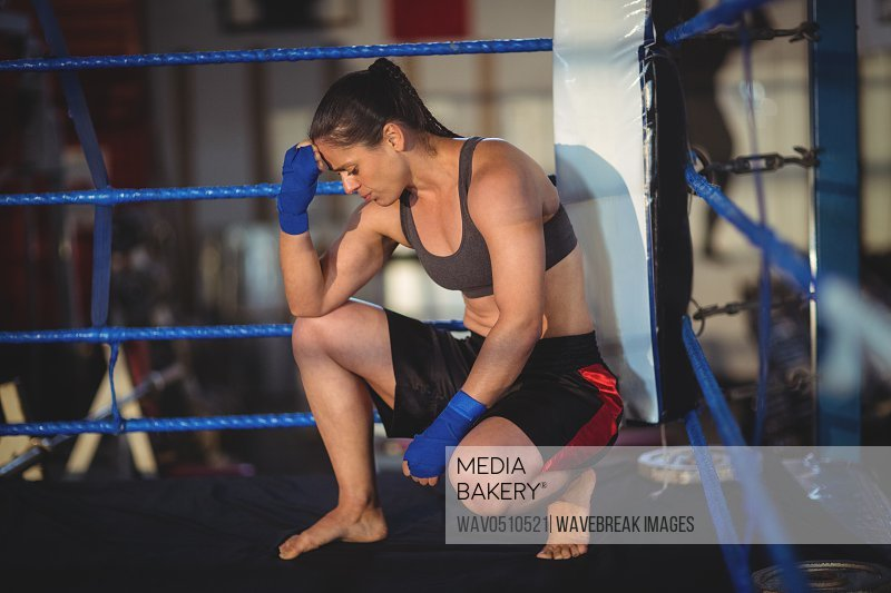 Stressed female boxer crouching in boxing ring