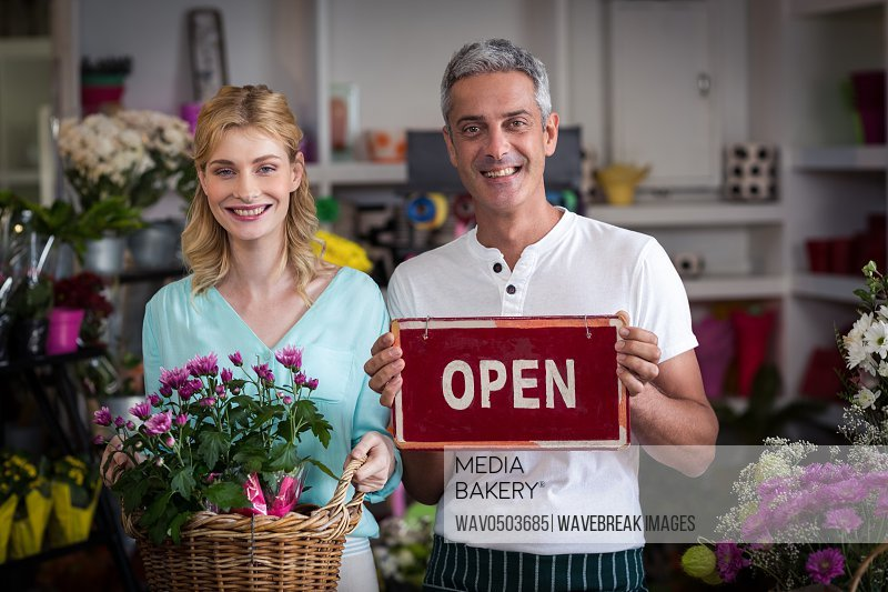 Portrait of smiling florists holding open sign placard and flower basket in flower shop