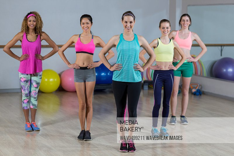 Portrait of group of fitness team standing with hands on hip in fitness studio