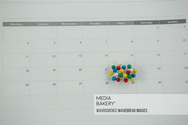 Close-up of multicolored push pin marked on calendar