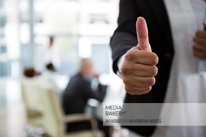 Mid section of businesswoman showing thumbs up in office