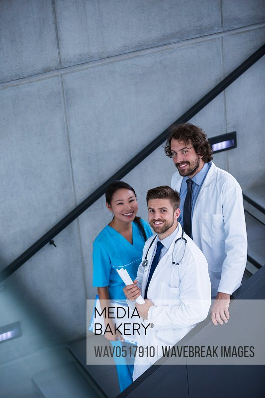 Doctors and nurse holding medical reports standing on stairs