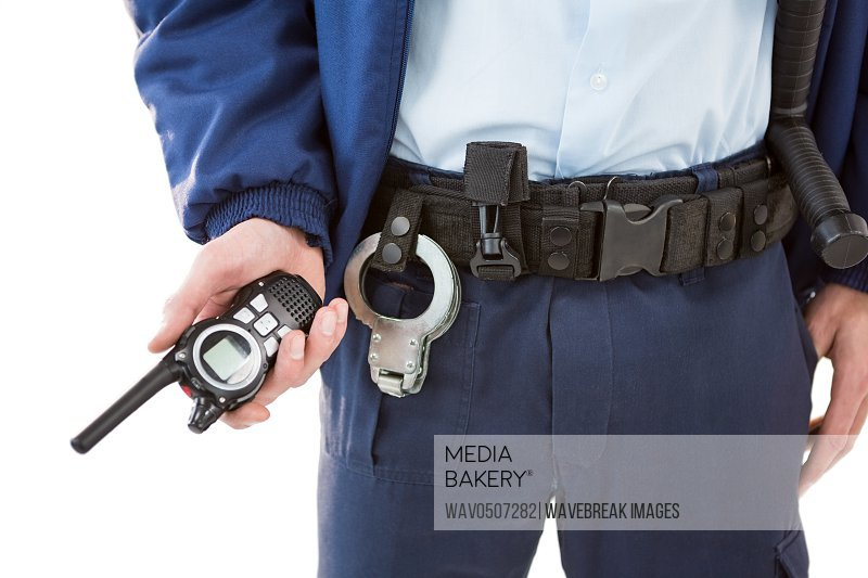 Mid section of security officer holding a walkie-talkie against white background