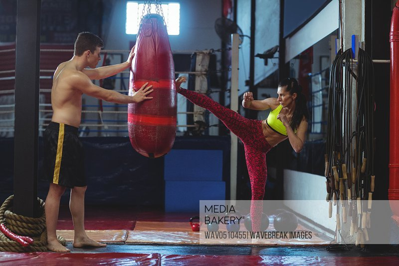 Female boxer practicing a kick boxing in fitness studio